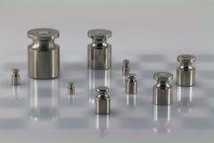 Grupo de pesos do ferro na superfície da luz com fundo do tabuleiro de xadrez Imagem de Stock Royalty Free