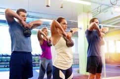 Grupo de pessoas com kettlebells que exercita no gym Foto de Stock