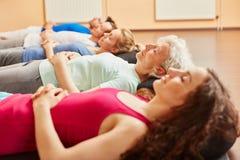 Grupo de pessoas com o sênior que faz o exercício de respiração