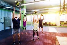 Grupo de pessoas com treinamento da bola de medicina no gym Imagem de Stock Royalty Free