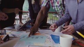 Grupo de pessoas da raça misturada do close-up que está perto da tabela Equipe nova do negócio que trabalha no projeto start-up j video estoque