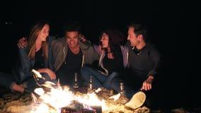 Grupo de pessoas diverso que senta-se junto pelo fogo tarde na noite e que abraça-se, cozinhando salsichas e filme
