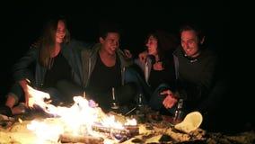 Grupo de pessoas diverso que senta-se junto pelo fogo tarde na noite e que abraça-se Fala alegre dos amigos video estoque
