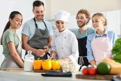 Grupo de pessoas e cozinheiro chefe fêmea foto de stock