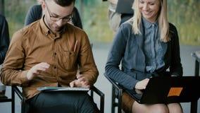 Grupo de pessoas feliz novo na reunião de negócios Homem e mulher que sorriem, usando dispositivos, portátil e a tabuleta digital video estoque