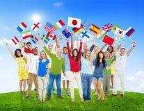 Grupo de pessoas multi-étnico que guarda bandeiras nacionais fora foto de stock royalty free