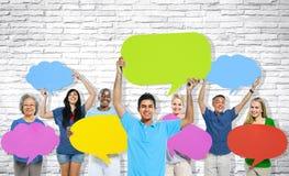 Grupo de pessoas multi-étnico que guarda bolhas coloridas do discurso fotos de stock