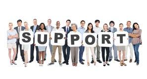 Grupo de pessoas multi-étnico que guarda o apoio das letras Fotografia de Stock