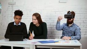 Grupo de pessoas multi-étnico que trabalha junto Um deles está usando vidros do vr Grupo diverso feliz de estudantes ou de jovens filme