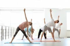 Grupo de pessoas na ioga praticando do sportswear foto de stock