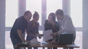 Grupo de pessoas no lugar de funcionamento durante a reunião incorporada em um escritório à moda com a grande janela panorâmico n fotografia de stock royalty free
