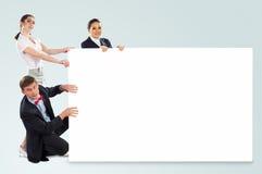 Grupo de pessoas pequeno que guarda uma bandeira vazia imagem de stock