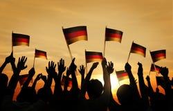 Grupo de pessoas que acena bandeiras alemãs no Lit traseiro imagem de stock royalty free