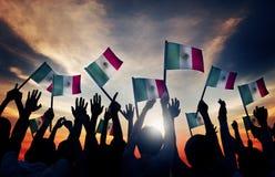 Grupo de pessoas que acena bandeiras mexicanas no Lit traseiro imagem de stock