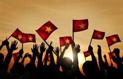 Grupo de pessoas que acena bandeiras vietnamianas no Lit traseiro imagem de stock