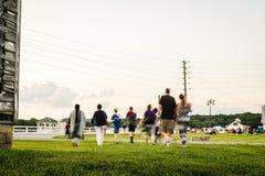 Grupo de pessoas que anda através de um parque a uma mostra exterior do concerto e dos fogos-de-artifício fotos de stock