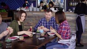 Grupo de pessoas que come junto no restaurante video estoque