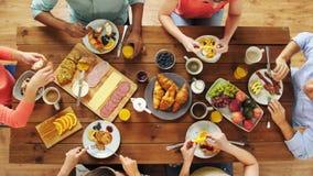 Grupo de pessoas que come na tabela com alimento vídeos de arquivo