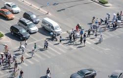 Grupo de pessoas que cruza uma avenida alta do tráfego no Pequim, China foto de stock