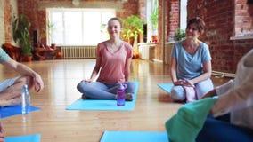 Grupo de pessoas que descansa em esteiras da ioga no gym video estoque