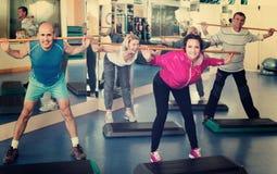 Grupo de pessoas que exercita em um clube de aptidão fotos de stock