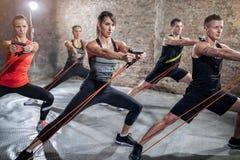 Grupo de pessoas que faz o exercício com faixa elástica imagem de stock royalty free