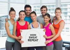Grupo de pessoas que guarda o cartão com trabalho, suor e repetição do texto na frente da janela no gym foto de stock
