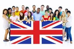 Grupo de pessoas que guarda a placa de Reino Unido imagens de stock royalty free