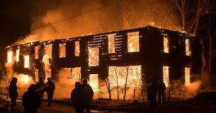 Grupo de pessoas que olha a casa no fogo Casa de madeira velha grande sobre imagem de stock