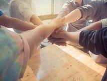 Grupo de pessoas que põe suas mãos que trabalham junto sobre b de madeira foto de stock royalty free