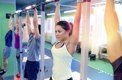 Grupo de pessoas que pendura na barra horizontal no gym Fotografia de Stock Royalty Free