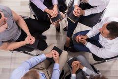 Grupo de pessoas que reza junto fotografia de stock