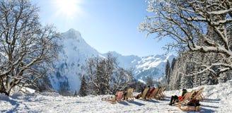 Grupo de pessoas que senta-se com as cadeiras de plataforma em montanhas do inverno Tomar sol na neve Alemanha, Baviera, Allgau Fotos de Stock Royalty Free