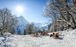 Grupo de pessoas que senta-se com as cadeiras de plataforma em montanhas do inverno Tomar sol na neve Alemanha, Baviera, Allgau Imagens de Stock