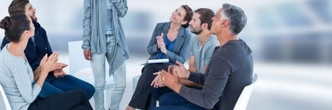 Grupo de pessoas que senta-se no círculo com o ladt que levantam-se e mãos de aplauso foto de stock