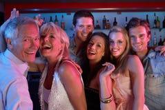 Grupo de pessoas que tem o divertimento na barra ocupada Fotos de Stock