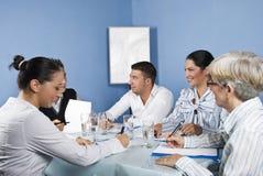 Grupo de pessoas que tem o divertimento na reunião de negócio Foto de Stock