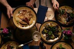 Grupo de pessoas que tem o jantar na tabela com alimento, vista superior foto de stock royalty free