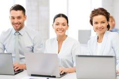 Grupo de pessoas que trabalha com os portáteis no escritório Imagens de Stock Royalty Free