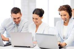 Grupo de pessoas que trabalha com os portáteis no escritório Fotografia de Stock Royalty Free