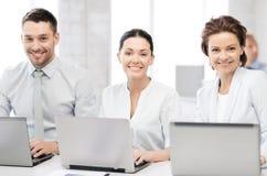 Grupo de pessoas que trabalha com os portáteis no escritório Fotos de Stock Royalty Free