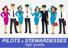 Grupo de pilotos e de duas comissárias de bordo no uniforme Fotos de Stock