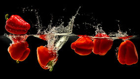 Grupo de pimenta de sino que cai na água com respingo no fundo preto fotografia de stock