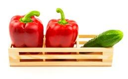 Grupo de pimentas vermelhas doces e de pepino fresco na caixa de madeira Imagem de Stock