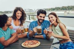 Grupo de povos alegres novos que comem a pizza e que bebem a cerveja ao sentar-se nos sacos de feijão no telhado fotos de stock royalty free