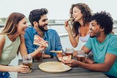 Grupo de povos alegres novos que comem a pizza e que bebem a cerveja ao sentar-se nos sacos de feijão no telhado imagem de stock royalty free
