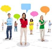 Grupo de povos alegres que usam dispositivos de Digitas com bolhas do discurso Imagens de Stock Royalty Free