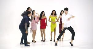 Grupo de povos asiáticos novos que têm o divertimento que dança como louco no fundo branco Povos com partido, celebração, aprecia video estoque