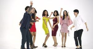 Grupo de povos asiáticos novos que têm o divertimento que dança como louco no fundo branco Povos com partido, celebração, aprecia vídeos de arquivo