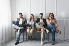 Grupo de povos criativos que sentam-se em cadeiras na sala de espera fotos de stock